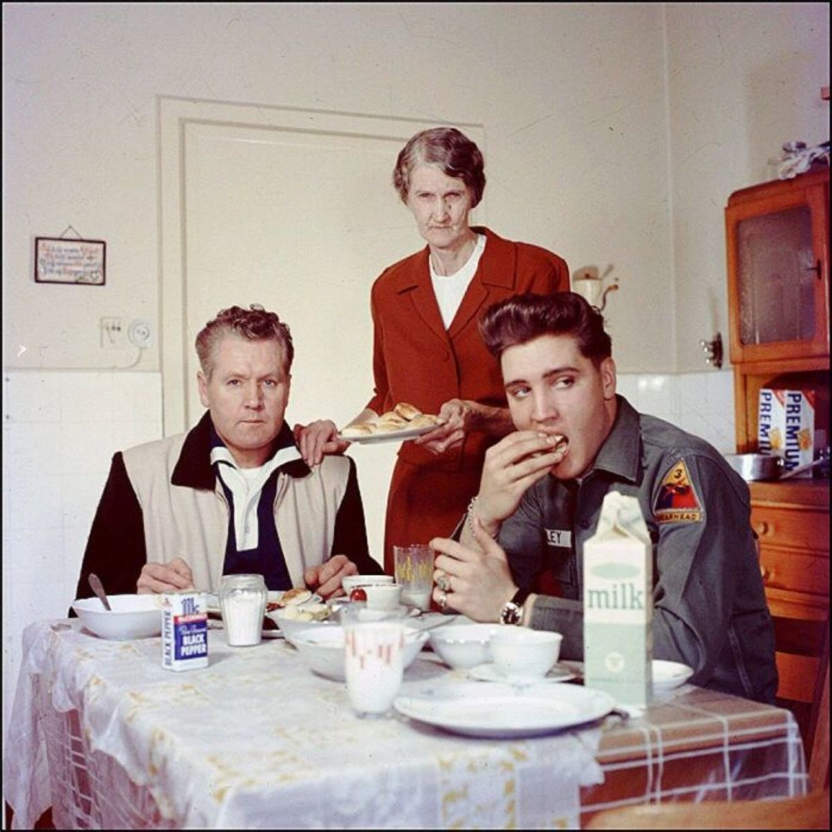 Elvis' parents look so disappointed. .. To me it looks like a photoshoot, you have the stern and angry looking parents and then the carefree and nonchalant Elvis eating and looking in the distance.